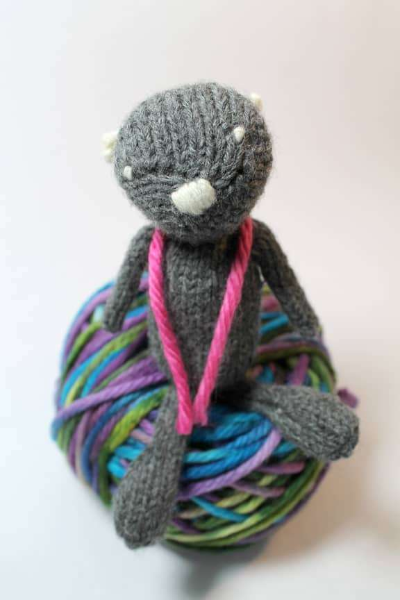 little bear sitting on a ball of yarn