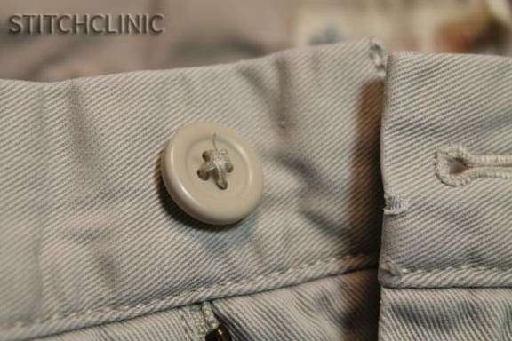 Close up of a button on an older pair of pants