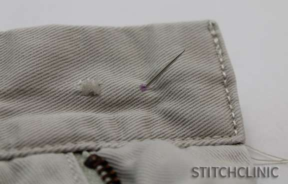 Pushing the hand needle through the fabric to start securing the button.