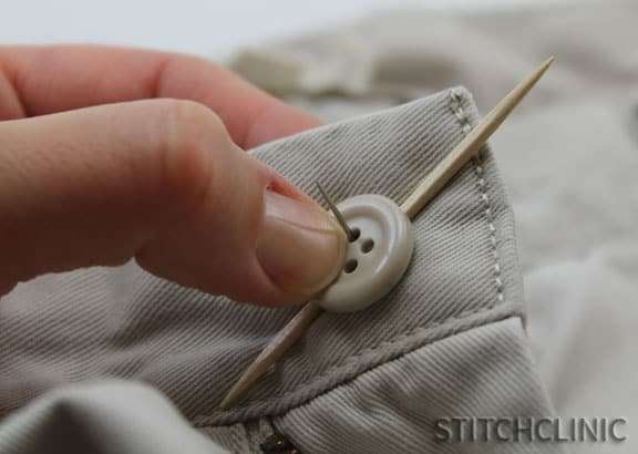 Holding a toothpick under the button to make space under the button when it is sewn on.