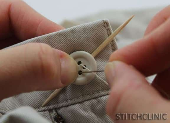 Insert threaded needle into button hole to start securing.