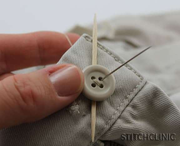 needle sticking out of other button hole.